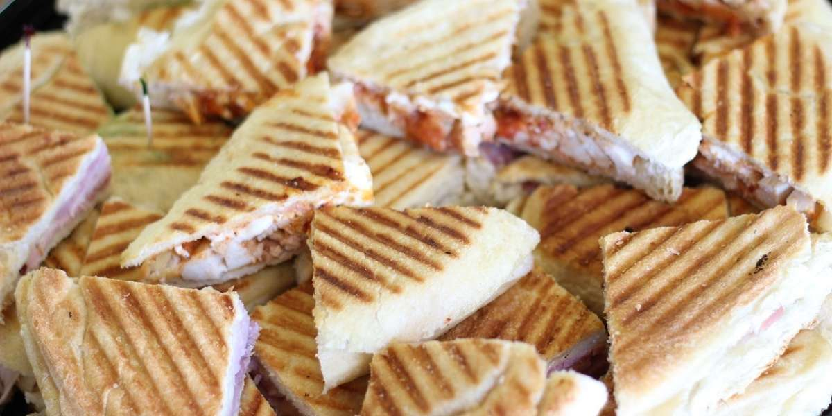 We don't claim to have invented the panini, but 'HOT DAMN' we perfected it.  Try our panini platters or boxed lunches for your next meeting or event and you won't be disappointed. If you're in the mood for some Italian favorites, Stefano's family package offers classic choices like stuffed shells and lasagna. - Stefano's Golden Baked Hams